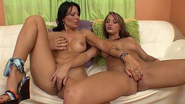 Two hot girls on the sofa rub on eachother's pussy and tits