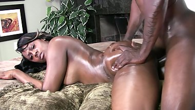 Playful black dude likes to oil his busty gf's butt before drilling her