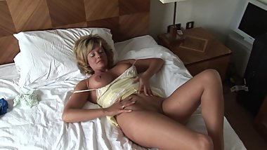 Busty mature blonde babe in slip and panties teases